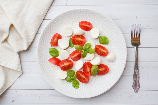 Caprese salad of tomatoes, mozzarella cheese and basil on a white plate. italian cuisine. Premium Photo