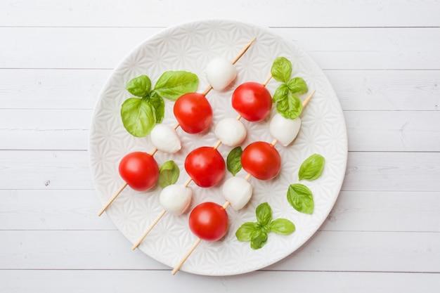 Caprese salad of tomatoes, mozzarella cheese and basil on a white plate. italian cuisine. Premium Photo