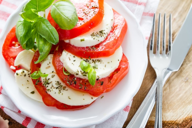Caprese salad on white plate, closeup Premium Photo