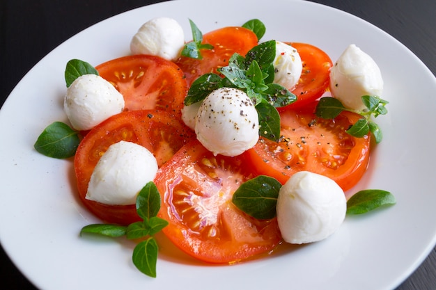 Caprese salad with ripe tomatoes and mozzarella with fresh basil leaves. italian food. Premium Photo
