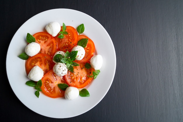 Caprese salad with ripe tomatoes and mozzarella with fresh basil leaves. italian food. Premium Photo