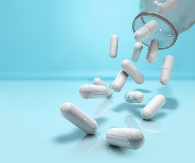 Capsules falling from glass bottle on blue background Premium Photo