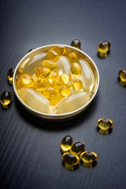 Capsules of fish oil in gold cup Premium Photo