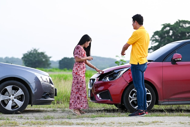 Car accident insurance.male female drivers  after traffic accident.people  after a car crash and trying to find friendly agreement Premium Photo