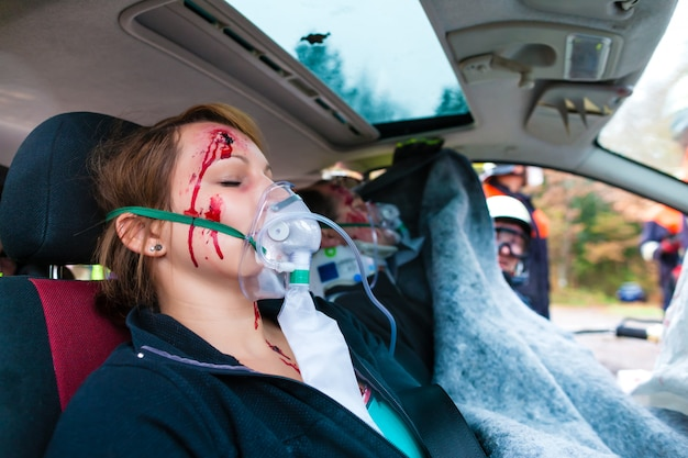 Car accident - victim in crashed vehicle receiving first aid Premium Photo
