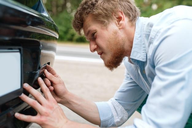 Поломка машины, молодой человек вкрутил буксирный крюк. Premium Фотографии
