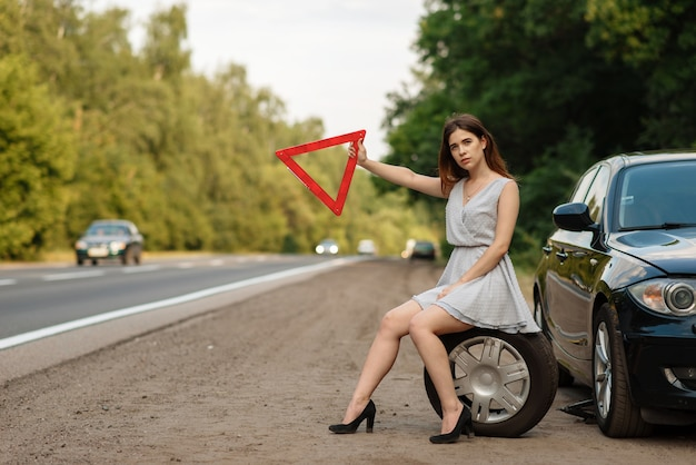 Car breakdown, young woman with emergency stop sign vote on the road Premium Photo