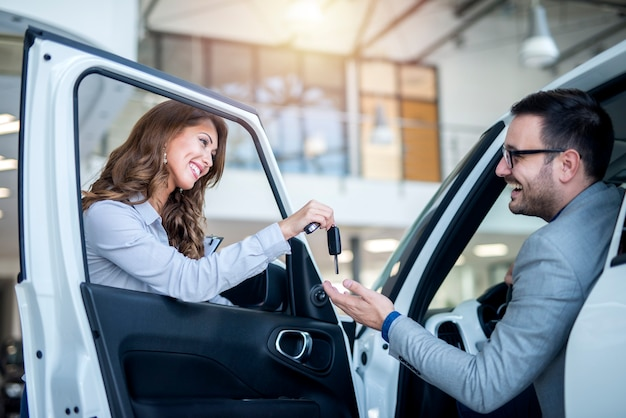 Concessionario auto e cliente presso showroom di veicoli scegliendo auto nuove Foto Gratuite