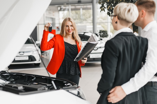 Car dealer holding a key and a documents and wide smiling  standing against couple. Premium Photo