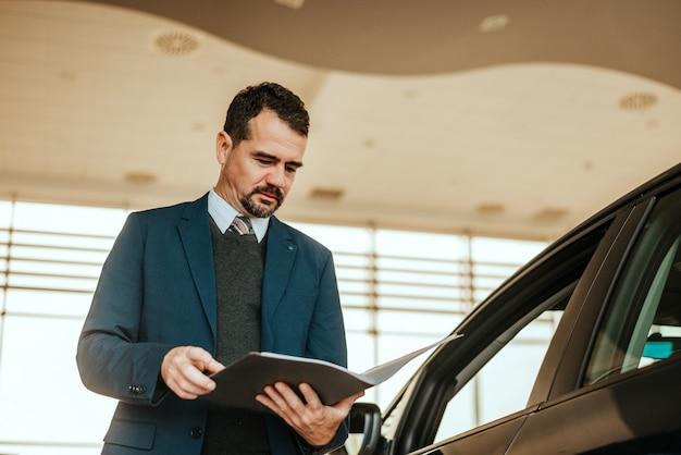 Car dealer looking at notepad in car salon. Premium Photo