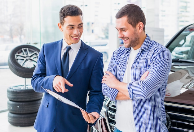 Car dealer talking to client Free Photo