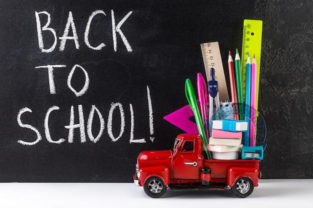 Car delivering school stationery against blackboard. education concept. Premium Photo