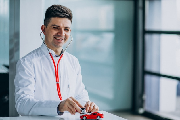 Car doctor with stethoscope in a car showroom Free Photo