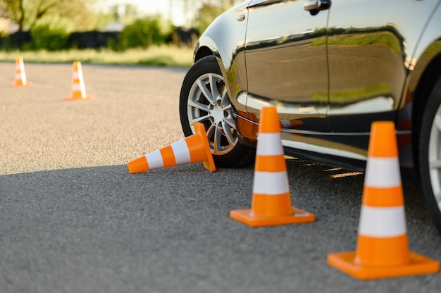 Car and downed traffic cone, lesson in driving school concept. Premium Photo