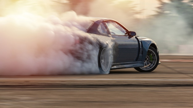 Car drifting, blurred  image diffusion race drift car with lots of smoke from burning tires Premium Photo