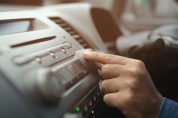 Car driver changing turning button radio stations on his vehicle Premium Photo