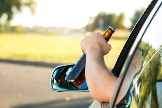 Car driver holding a bottle of beer Premium Photo