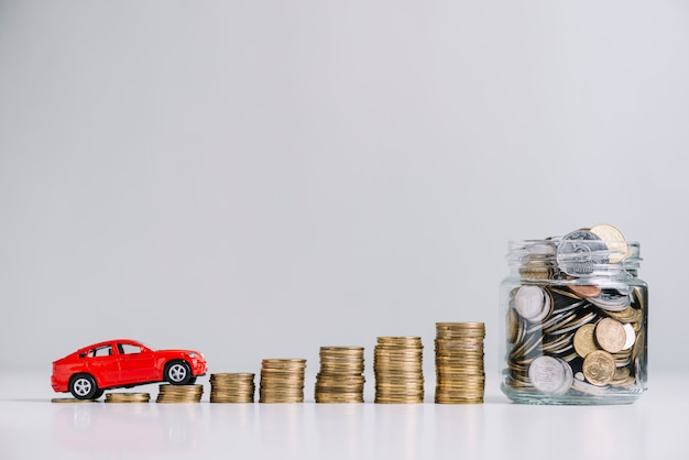 Car driving over increasing stacked coins near glass jar Free Photo