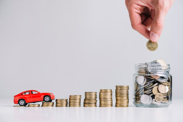 Car driving over increasing stacked coins near person's hand putting coin in glass jar Free Photo
