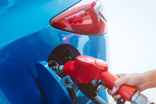Car fueling at gas station. refuel fill up with petrol gasoline. petrol pump filling fuel nozzle in fuel tank of car at gas station. petrol industry and service. Premium Photo
