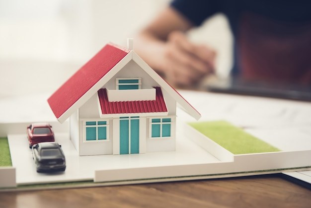 Car and house model on the table with blur working people Premium Photo