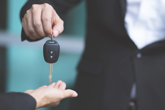 Car key, businessman handing over gives the car key to the other woman Premium Photo