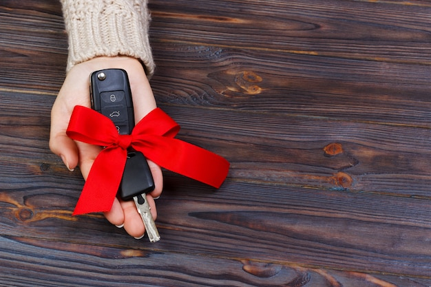 Car key with red bow in woomen hand on wooden background. valentine's day concept Premium Photo