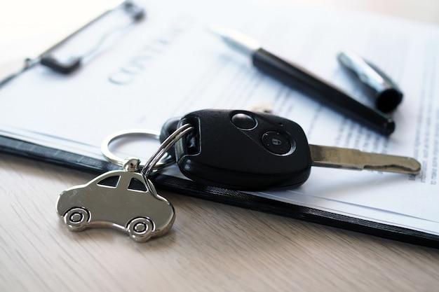 自動車ローンに関する契約書に配置された自動車の鍵。 Premium写真