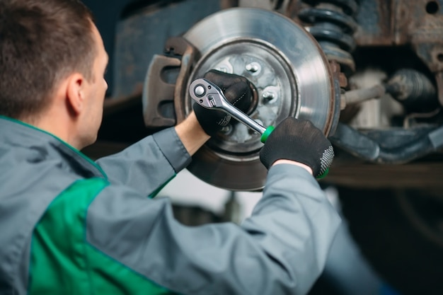 Car lifted in automobile service for fixing, worker repairs the wheel Premium Photo