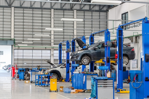 Car in the lifting equipment in the garage being repair and fix Premium Photo