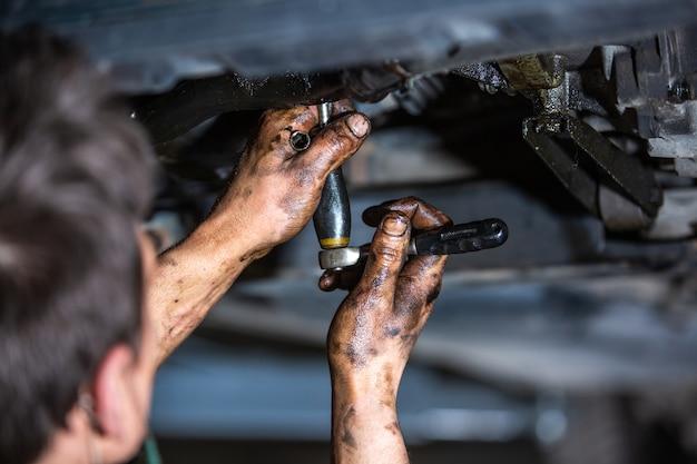 Car mechanic doing repair, maintenance oil change to the car on the hydraulic car lift, car vehicle service Premium Photo