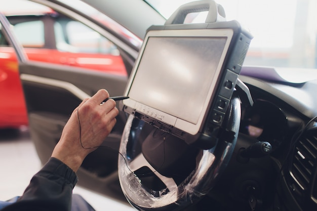Car mechanic maintains a vehicle with the help of a diagnostic computer - modern technology in the car repair shop. Premium Photo