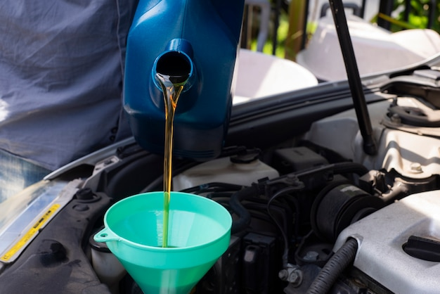 Car mechanic replacing and pouring fresh oil into engine at maintenance repair Premium Photo