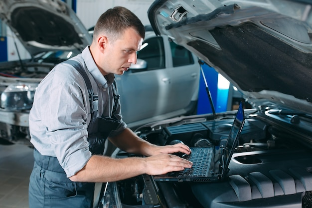 Premium Photo | Car mechanic using a computer laptop to diagnosing and  checking up on car engines parts for fixing and repair.