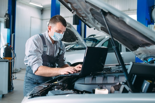 Car mechanic using a computer laptop to diagnosing and checking up on car engines parts for fixing and repair Premium Photo