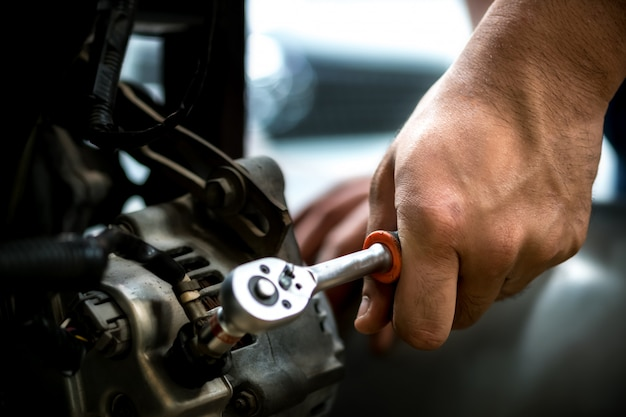 Car mechanic using a wrench dynamo auto repair. Premium Photo