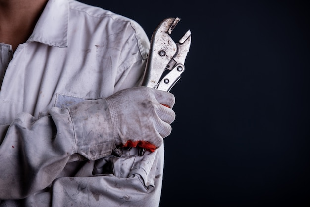 Car mechanic wearing a white uniform stand holding wrench Free Photo