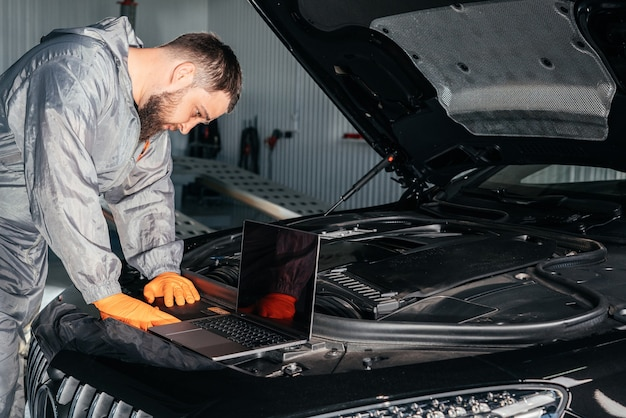 Автомеханик, работающий с ноутбуком в авторемонтной службе, проверка двигателя автомобиля Premium Фотографии