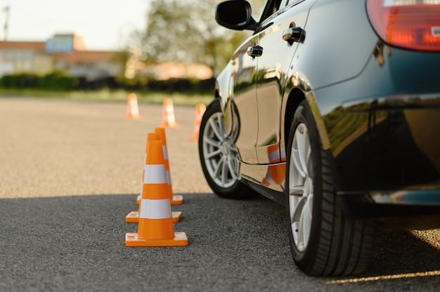 Car and orange traffic cones, lesson in driving school concept. Premium Photo