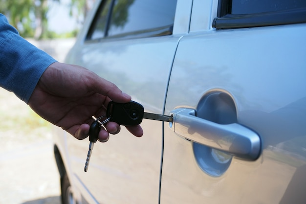 The car owner uses the key to open the car door. Premium Photo