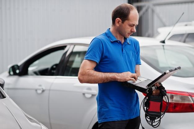 車の修理とメンテナンスのテーマ。自動車整備士の制服を着た電気整備士が、ラップトップでobdデバイスを使用して車の診断を行います。 Premium写真