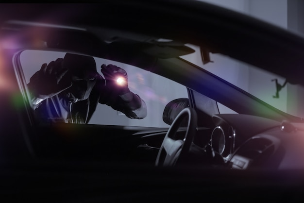 Car robber with flashlight Free Photo