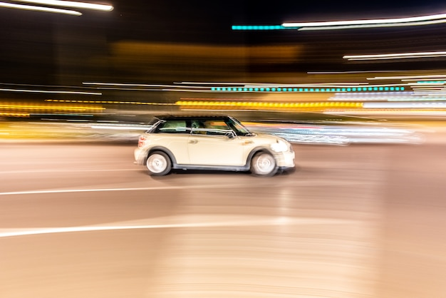 Car rolling at full speed through the city at night Premium Photo