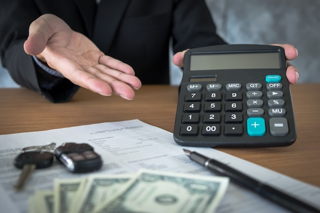 Car salesman holding a key and calculating a price at the dealership office Free Photo
