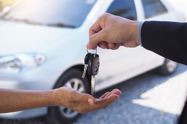 The car salesman and the key to the new owner. Premium Photo