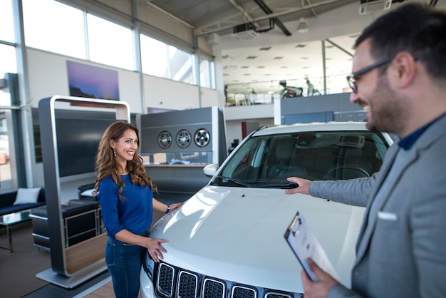 Car salesman presenting vehicle to the customer Free Photo