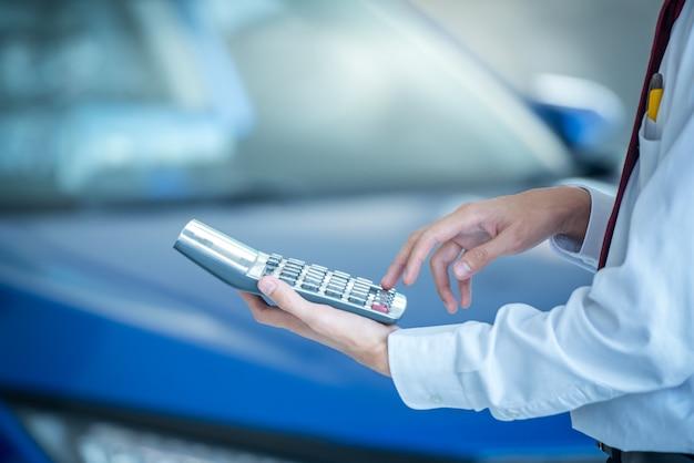 車のショールームでビジネスファイナンスの車のセールスマンを押す電卓新しい青い車ぼやけて背景。 Premium写真