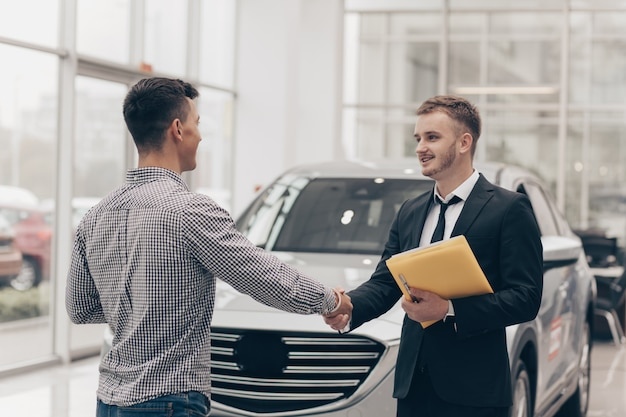 Car salesman working with a customer at the dealership Premium Photo