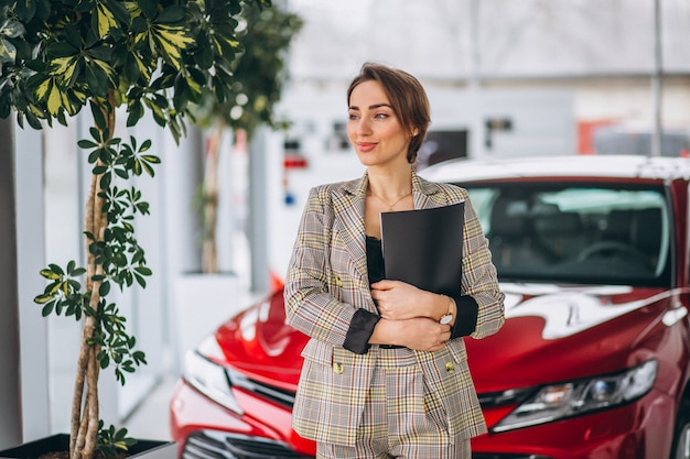 Car saleswoman in a car showroom Free Photo