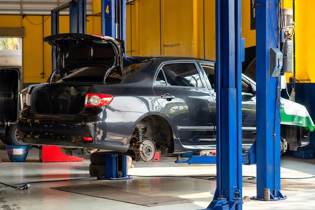 Car at service center. vehicle raised on a lift. check up, maintenance and repair concept Premium Photo